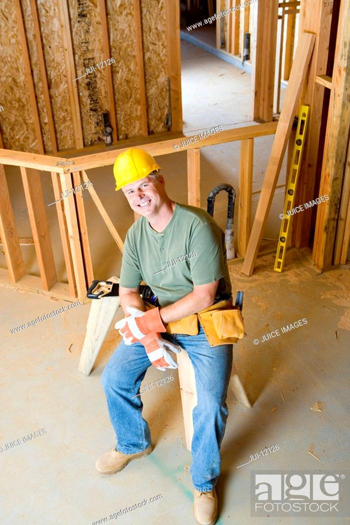 Stock Photo: Builder on site in hardhat, smiling, portrait, elevated view.