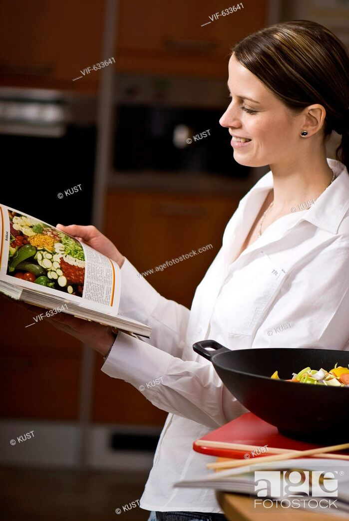 Imagen: junge Frau sucht Wokgericht in einem Kochbuch - Nieder÷sterreich, Ísterreich, 14/02/2008.