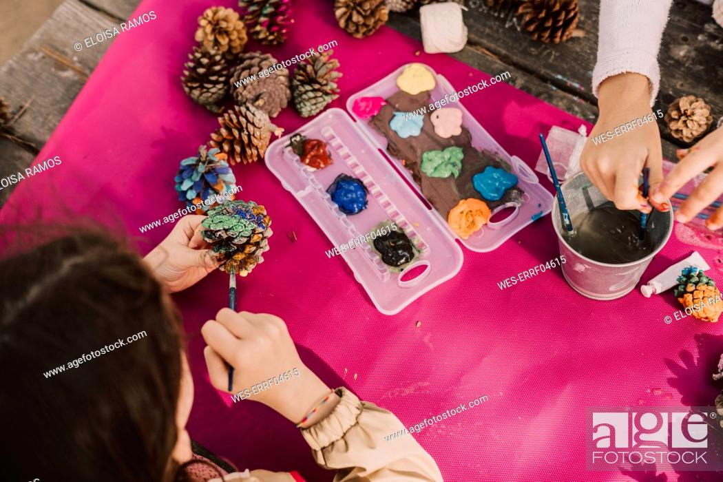 Stock Photo: Sisters coloring pine cones while decorating at picnic table in park.