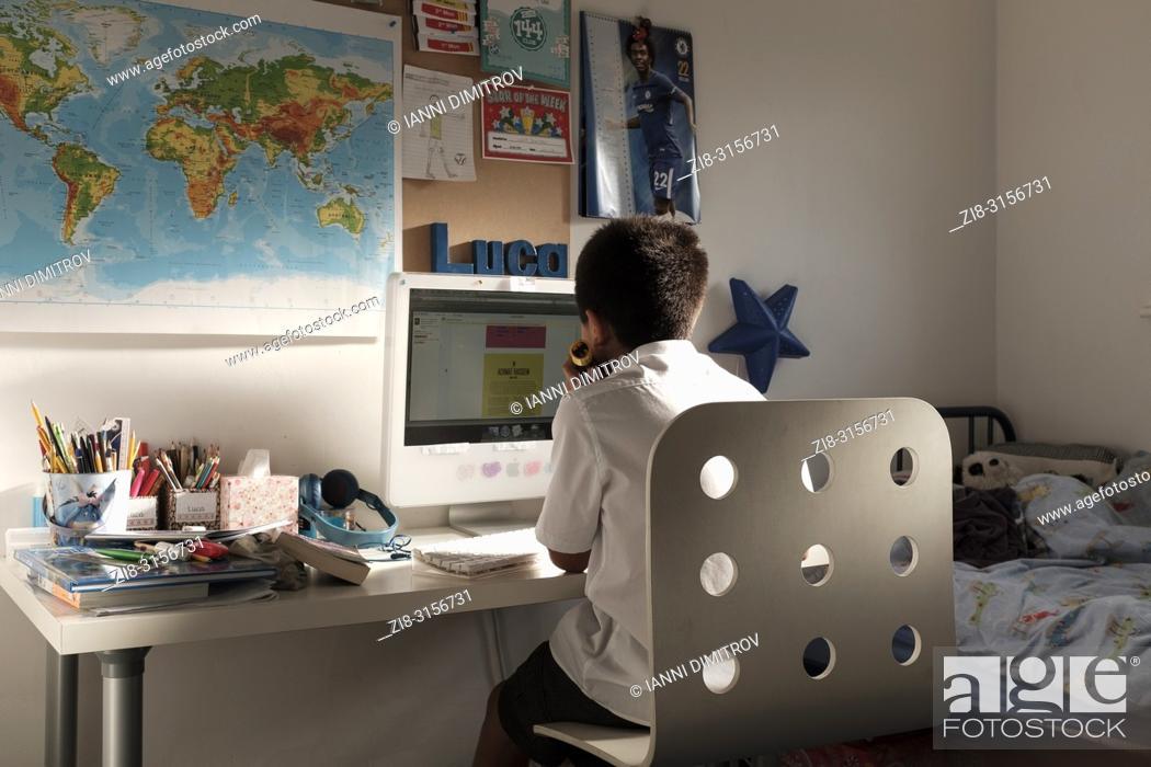 Stock Photo: UK, Surrey-Schoolboy-11 years old, studies nin his room.