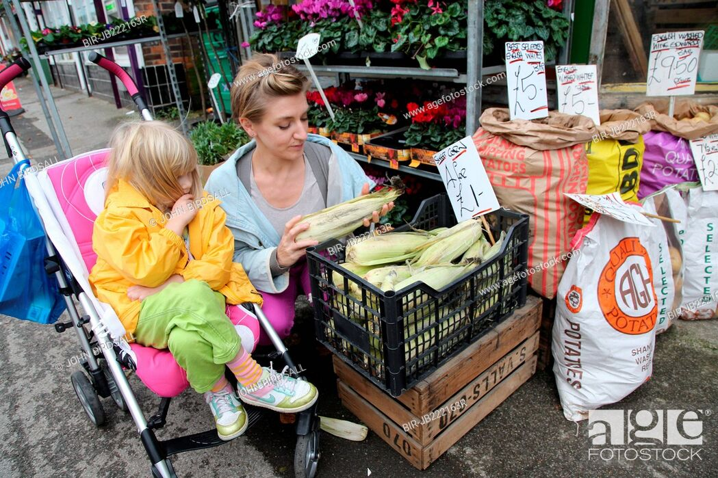 Imagen: Mother with toddler in buggy choosing vegetables.