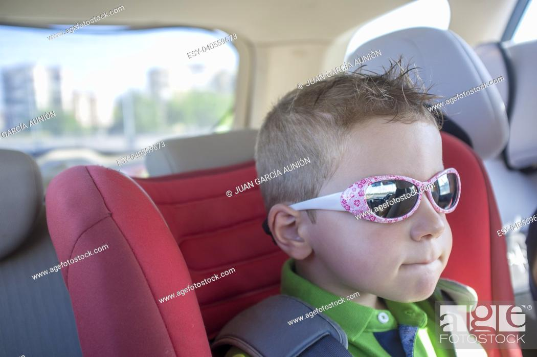Stock Photo: Handsome child boy wearing sunglasses inside the car. Protection of eyes during car trips concept.