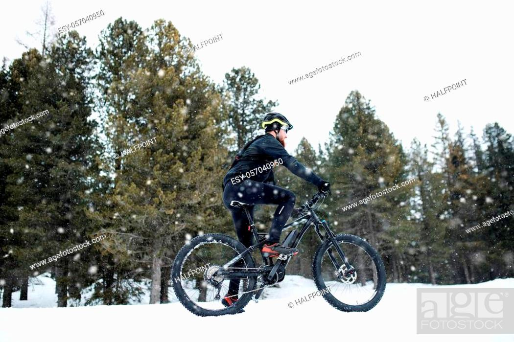 Imagen: A side view of mountain biker riding in snow outdoors in winter nature.
