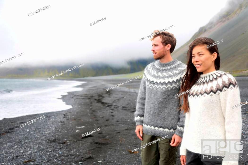 Imagen: Iceland couple wearing Icelandic sweaters on black sand beach. Woman and man model in typical Icelandic sweater looking at ocean enjoying view of nature.