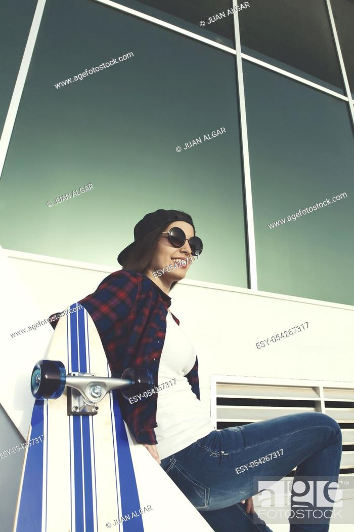 Stock Photo: Shot of smiling female in sunglasses sitting on stairs near skate.