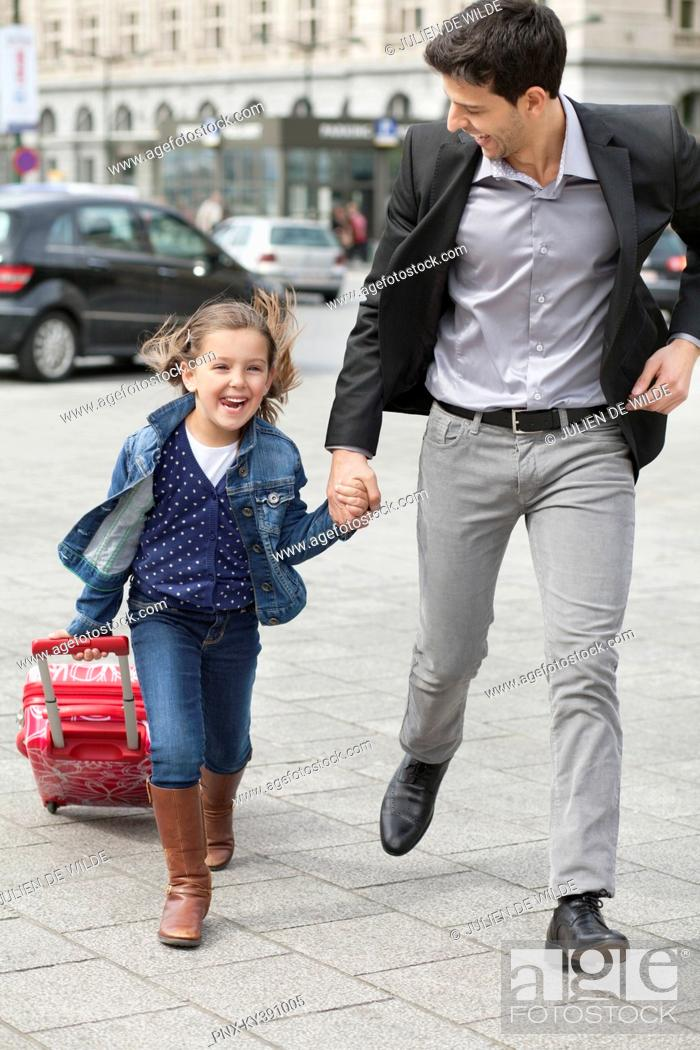 Stock Photo: Girl pulling a trolley bag while running with her father.