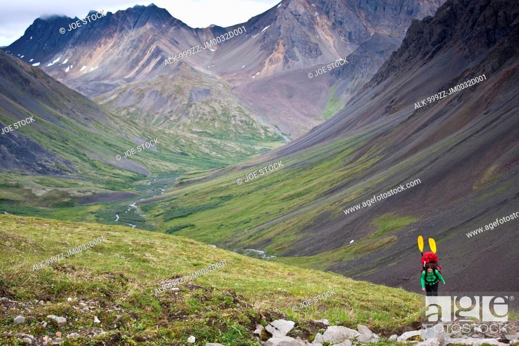 Photo de stock: Woman with a packraft hiking upper Windy Creek to a mountain pass under cloudy skies, Denali National Park & Preserve, Alaska Range, Interior Alaska, Summer.