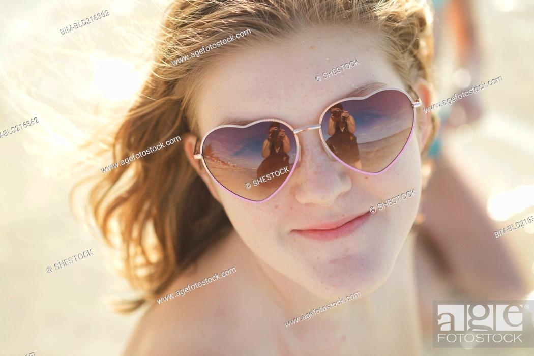 7727fbd86aa09 Stock Photo - Caucasian teenage girl wearing heart-shaped sunglasses