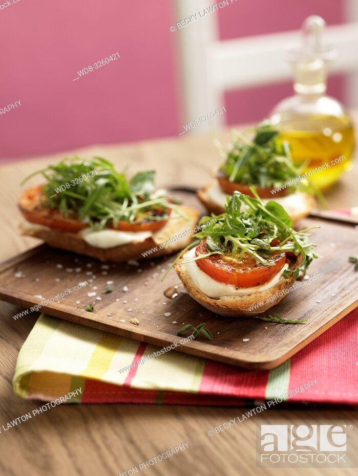 Imagen: tostada de pan con mozzarella, tomate asado, rucula y hierbas aromaticas.