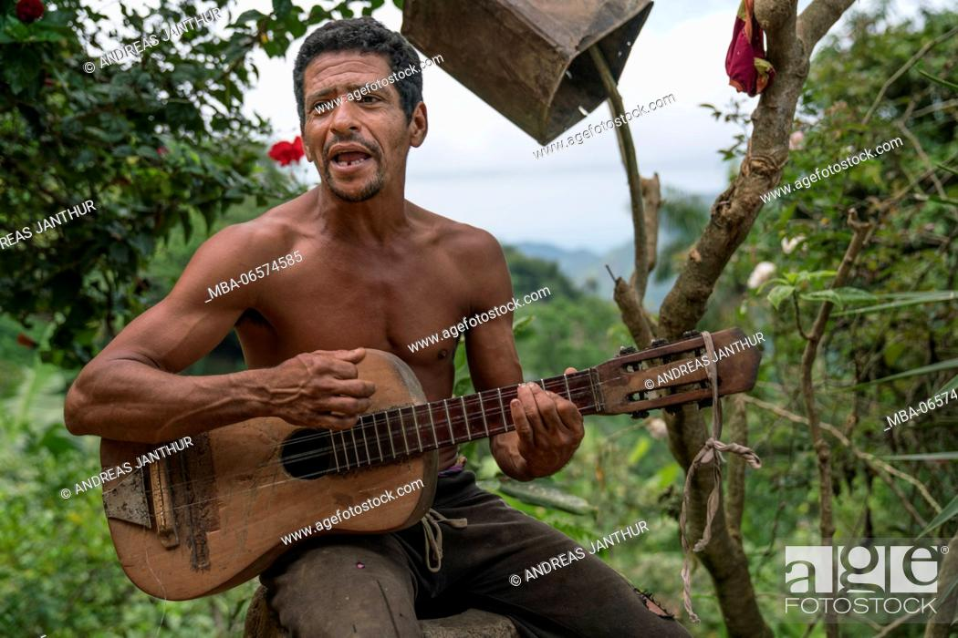 Stock Photo: A man playimg on a self-built guitar, mountain farm in the Sierra Maestra.