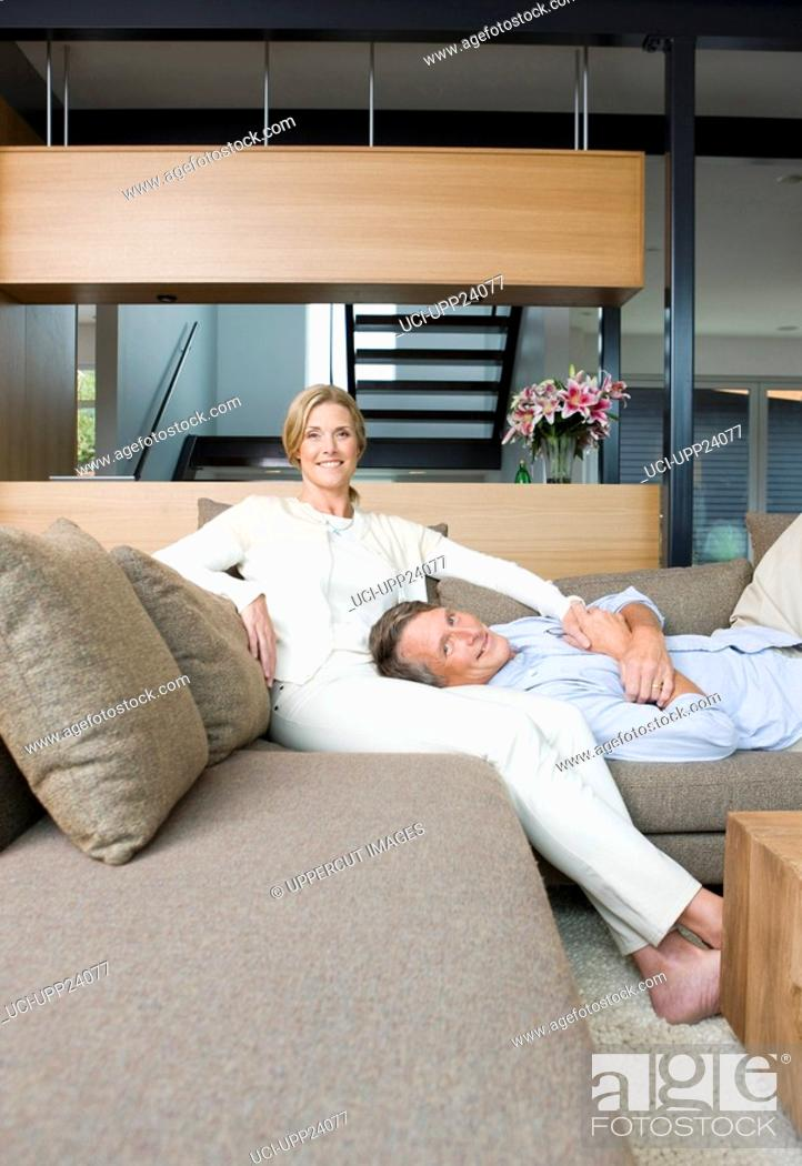 Stock Photo: Portrait of couple on sofa in living room.