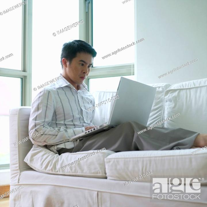 Stock Photo: Young man sitting on a couch using a laptop.