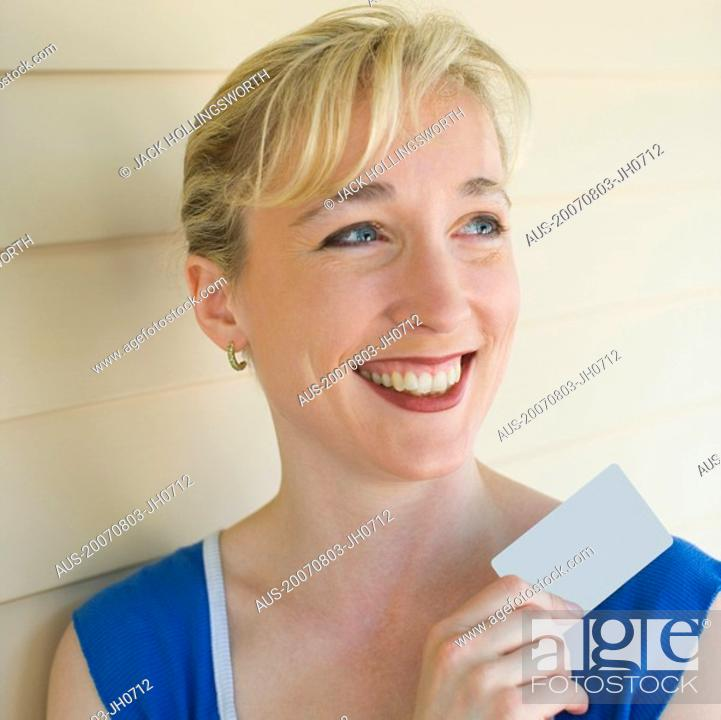 Stock Photo: Close-up of a mid adult woman holding a credit card and smiling.