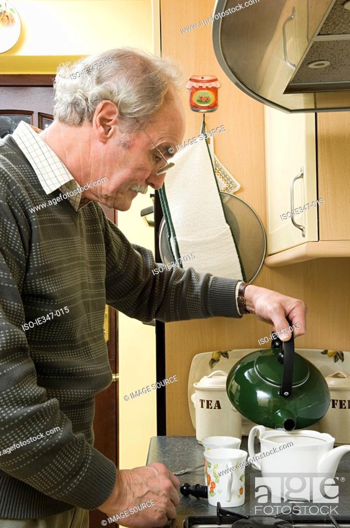 Stock Photo: Senior man making tea.