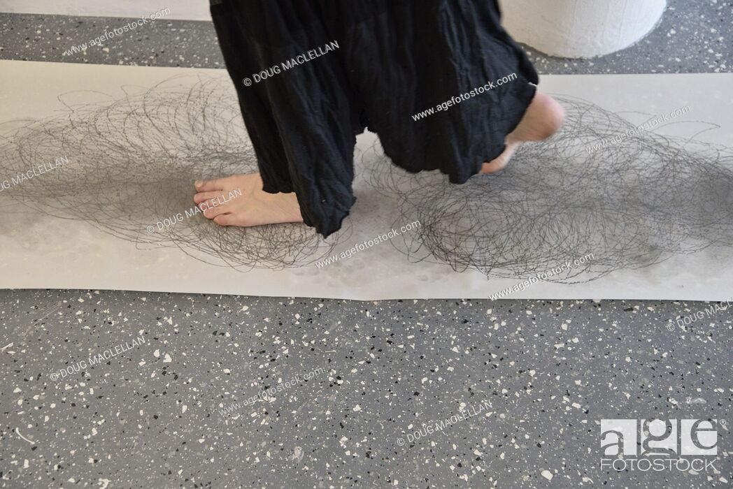 Stock Photo: A side view from the knees down of a woman artist in a black dress as she creates a performance art work at an artist run gallery in Windsor, Canada.