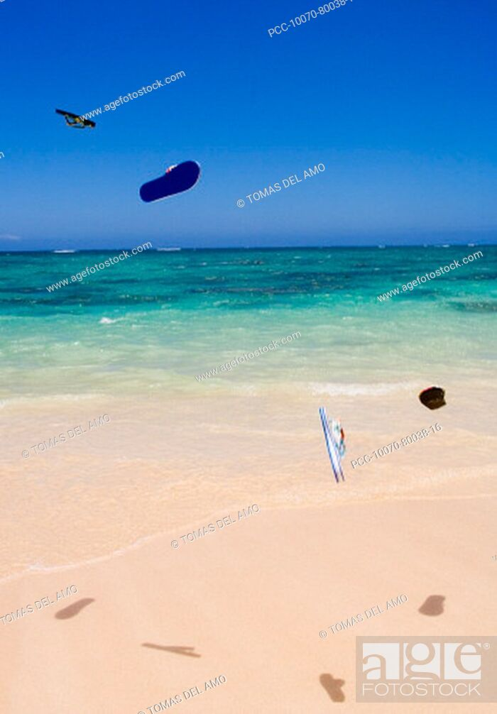 Stock Photo: Flipflops flying through the air above turquoise ocean and white sand beach.
