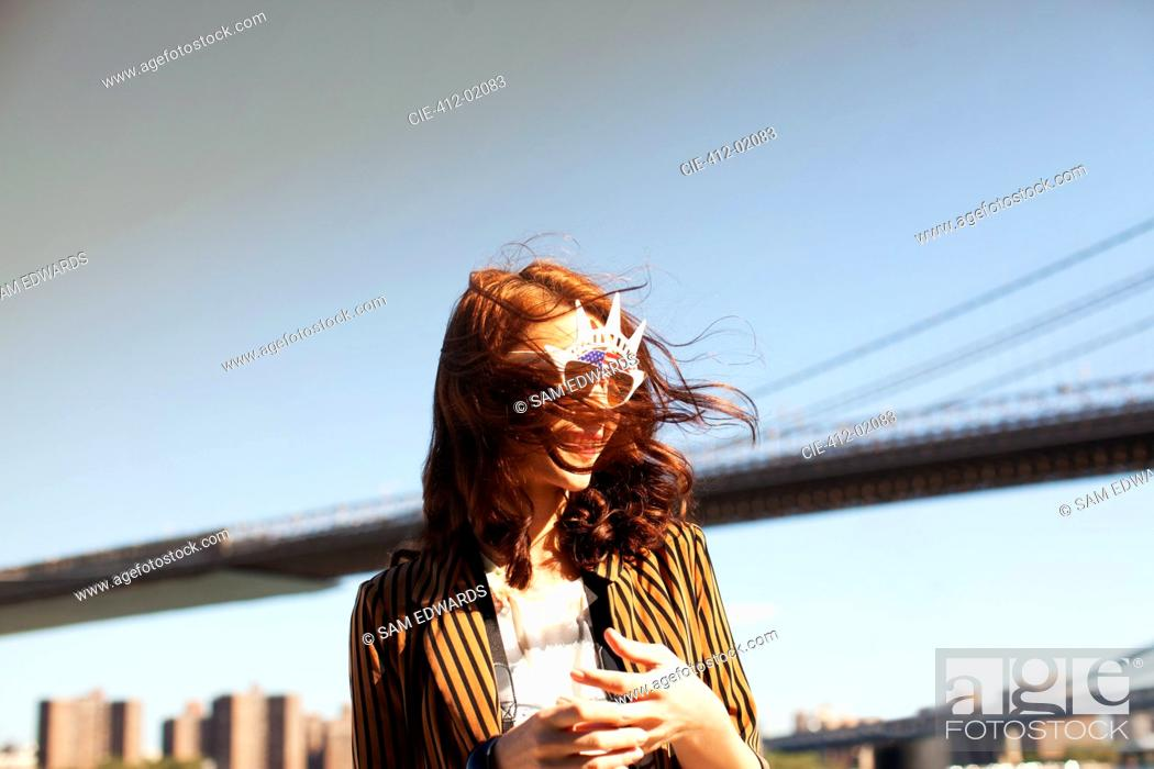Stock Photo: Woman in novelty sunglasses by city cityscape.