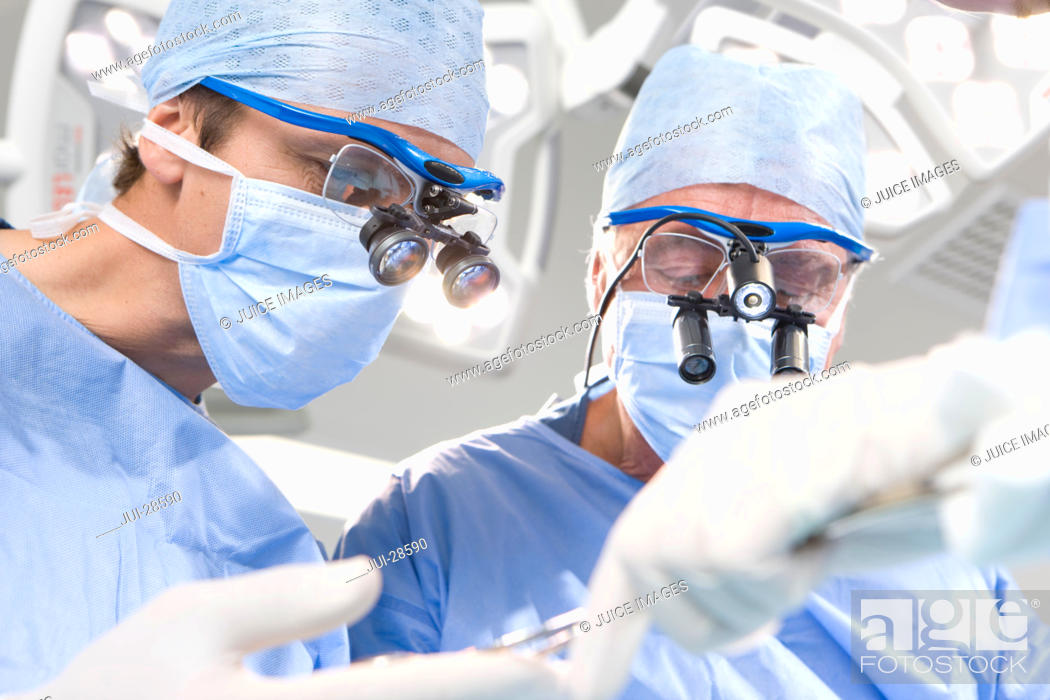 Imagen: Concentrating surgeons performing operation in operating room.