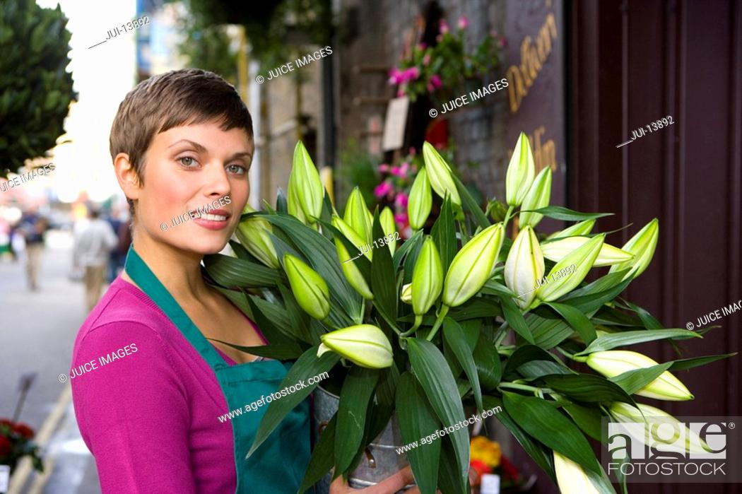 Stock Photo: Female florist with bunch of flowers, smiling, portrait.