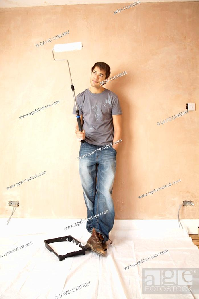 Stock Photo: Man standing with paint roller in unrenovated room portrait.