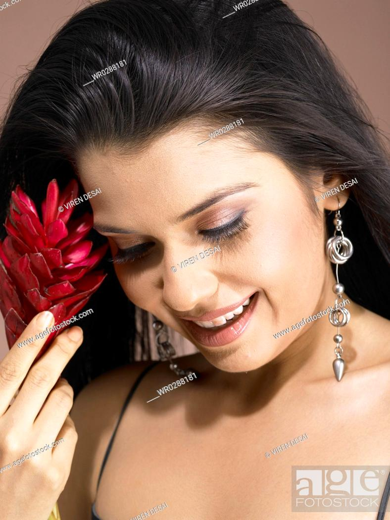 Stock Photo: South Asian Indian woman holding ginger flower and smiling MR 702.