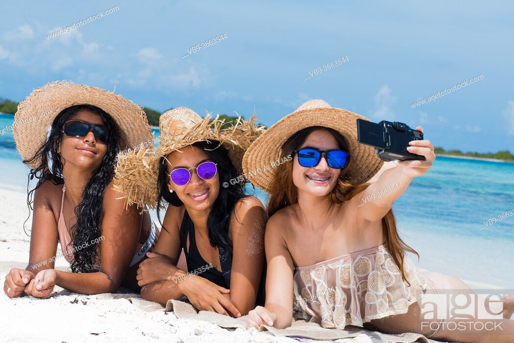 Photo de stock: Three multiracial happy girls friends in summer clothes taking a selfie at the beach in Los Roques venezuela.