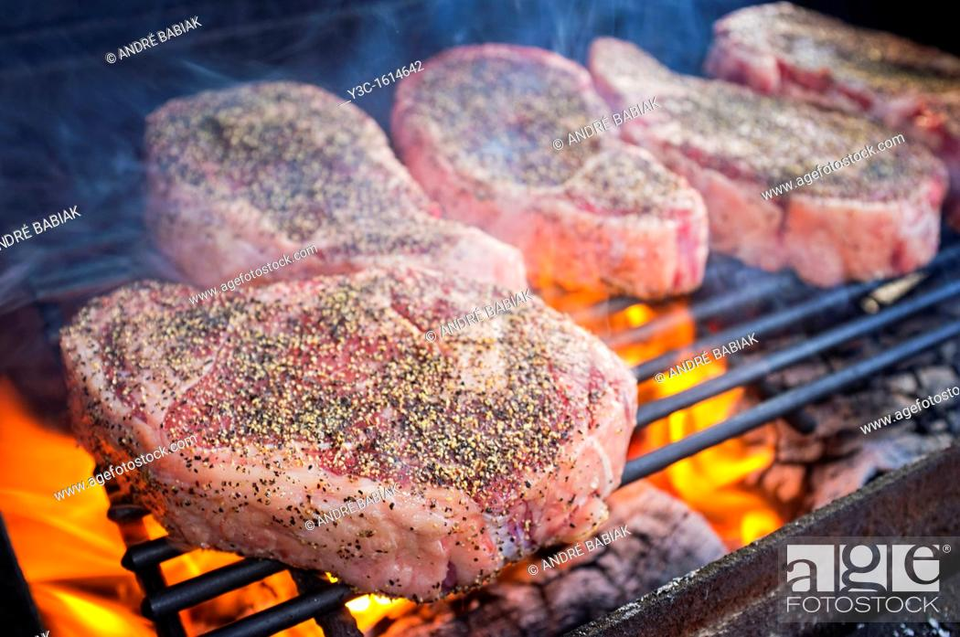 Stock Photo: Beef Ribeye Steaks grilling over hot fire.