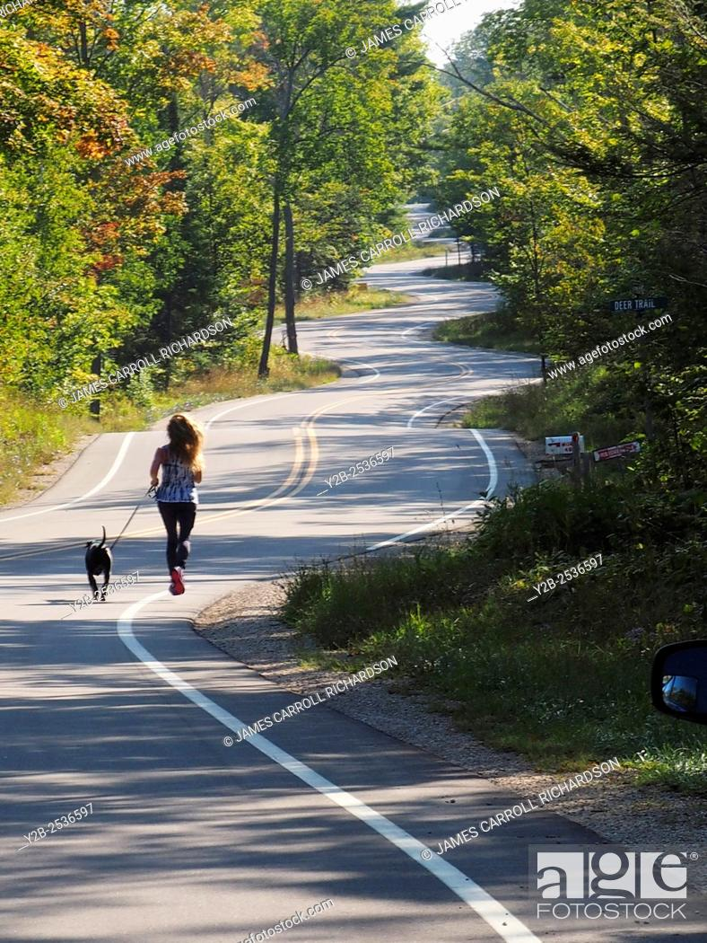 Stock Photo: Wisconsin Door County Elison Bay Windy Road with female runner and dog.