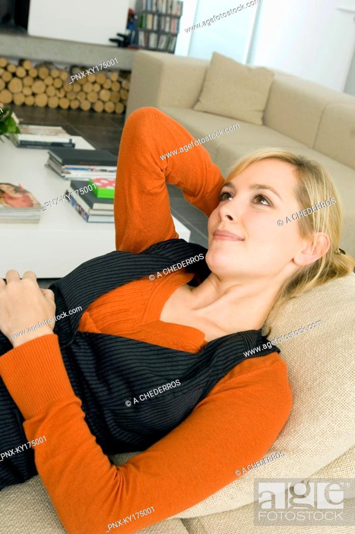 Stock Photo: Close-up of a young woman lying on a couch and thinking.