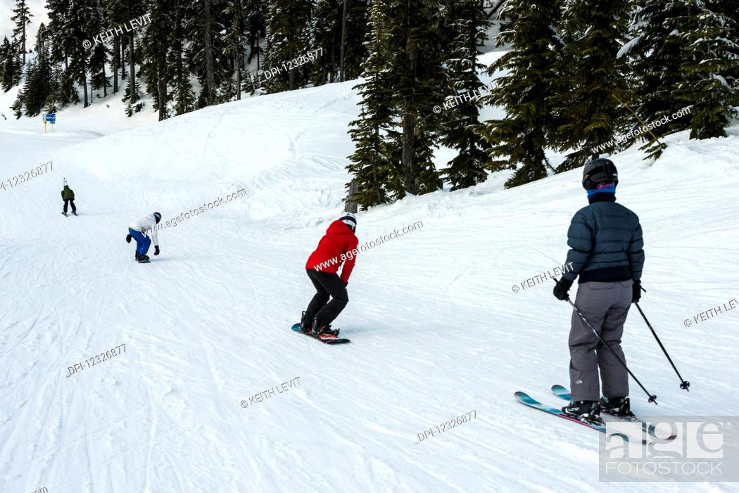 Photo de stock: A group of skiers and snowboarders making their way down a hill; Whistler, British Columbia, Canada.