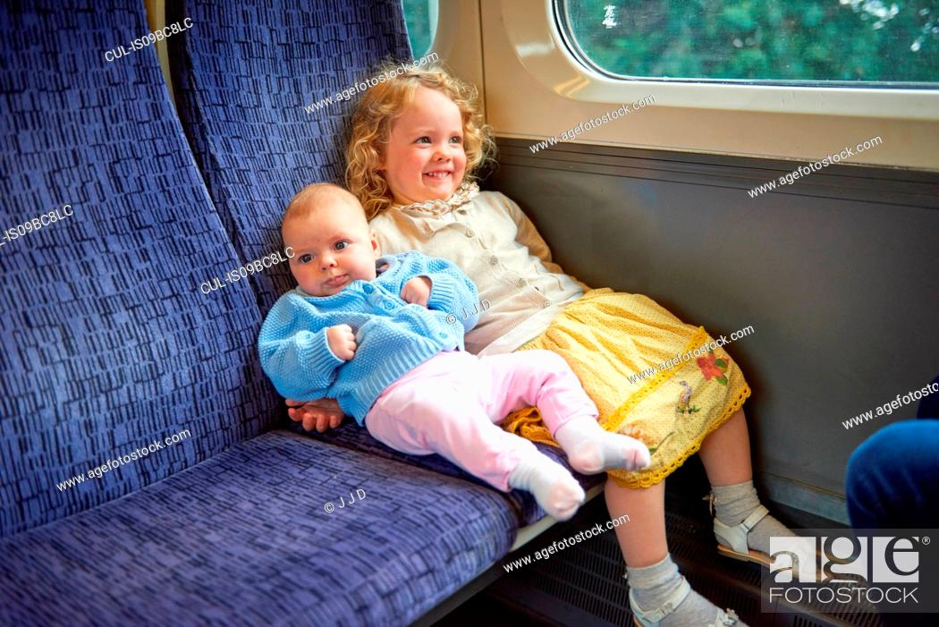 Stock Photo: Female toddler sitting on train with baby sister.