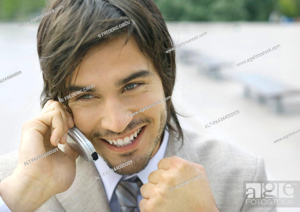 Stock Photo: Businessman using cell phone, smiling, and clenching fist.