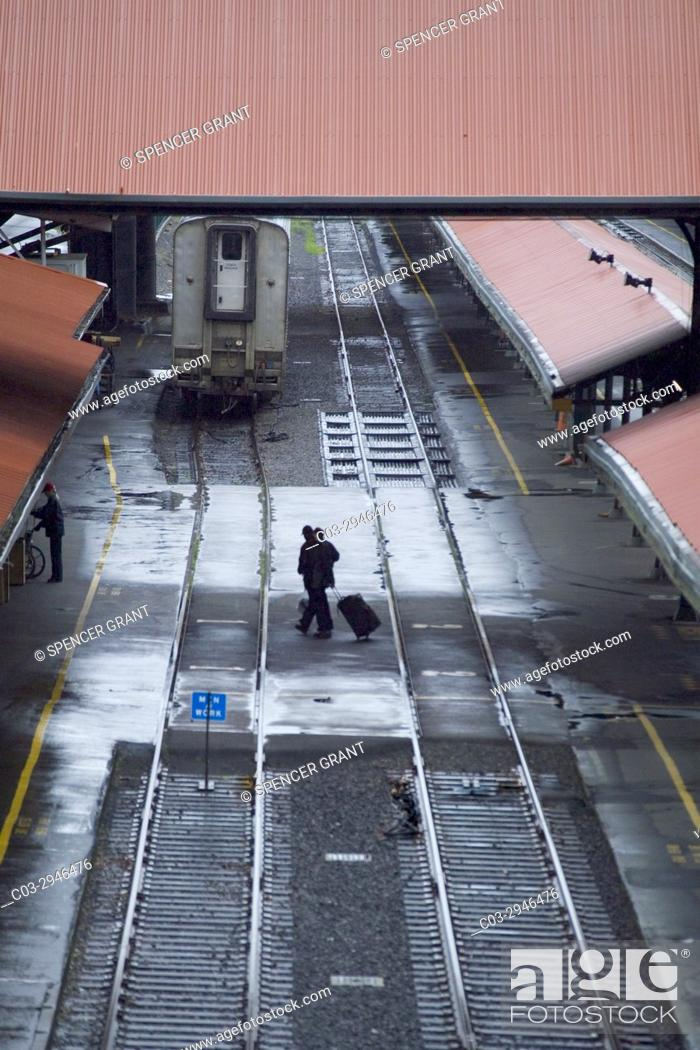 Stock Photo: Wheeling their luggage, arriving passengers cross railroad station tracks in Portland, OR.