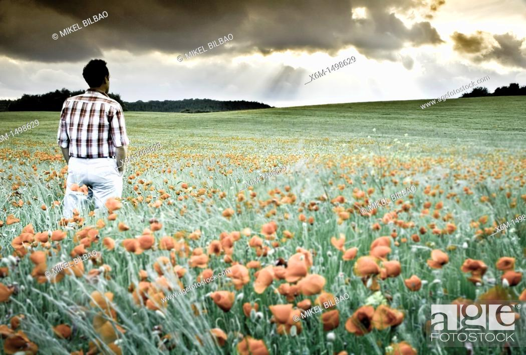 Stock Photo: Young man looking the storm on a grassland.