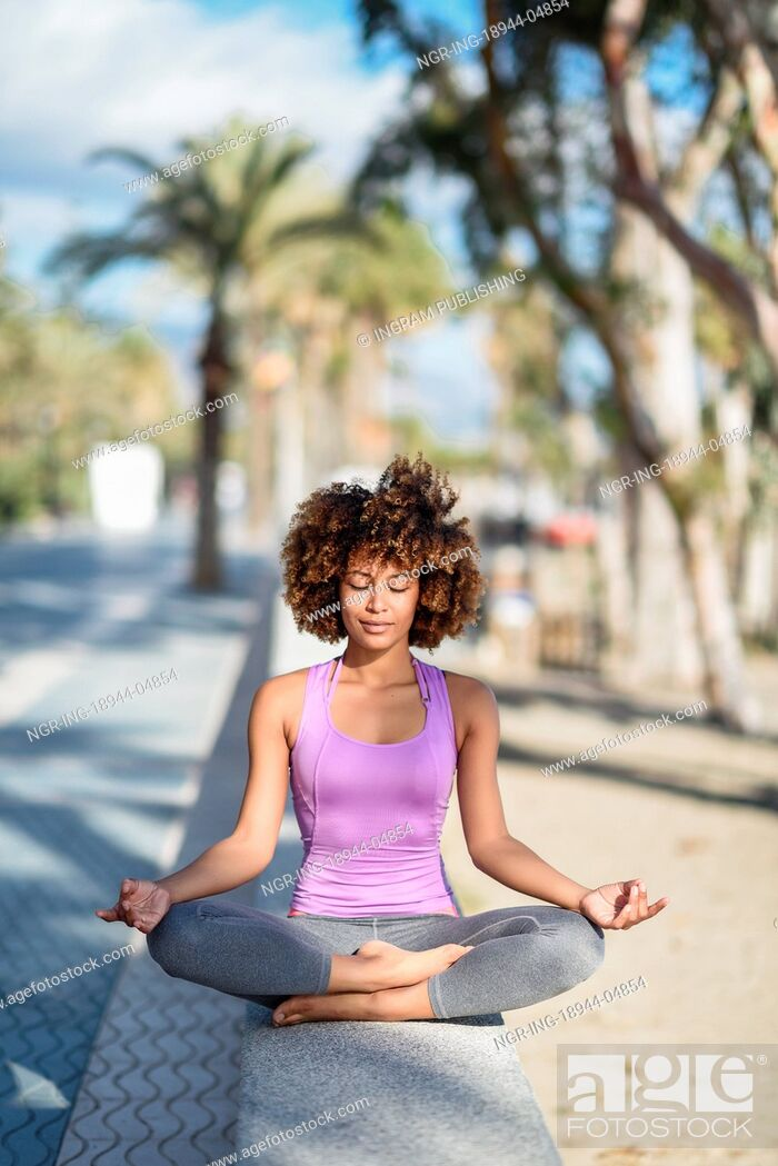 Stock Photo: Black woman, afro hairstyle, doing yoga asana in the beach with eyes closed. Young Female wearing sport clothes in lotus pose with defocused background.