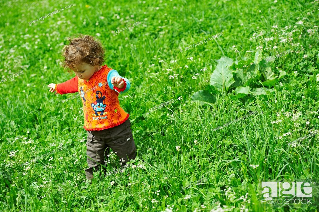 Stock Photo: A one year old baby girl playing in a green meadow.