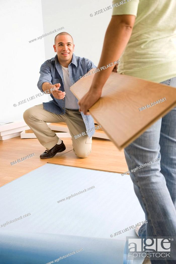 Stock Photo: African American couple installing flooring.