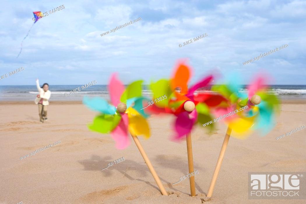 Stock Photo: Pinwheels on beach, girl 5-7 flying kite in background blurred motion.