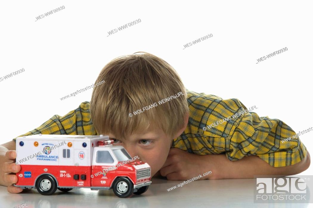 Stock Photo: Boy 8-9 playing with toy car.