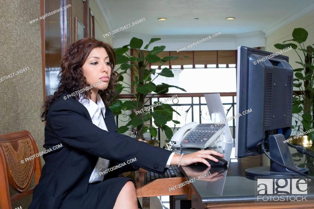 Stock Photo: Side profile of a female receptionist working on a desktop PC in a hotel reception.