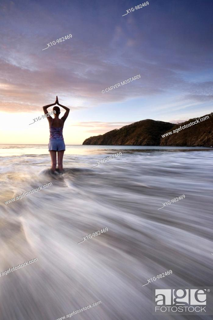 Stock Photo: Silhouette of young woman doing yoga at the beach during sunset in Playas del Coco, Costa Rica.