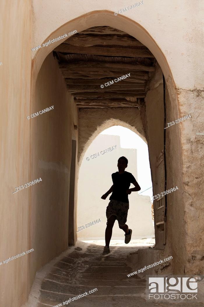 Stock Photo: Silhouette of a young man running through an archway at the old town Chora, Ios, Cyclades Islands, Greek Islands, Greece, Europe.