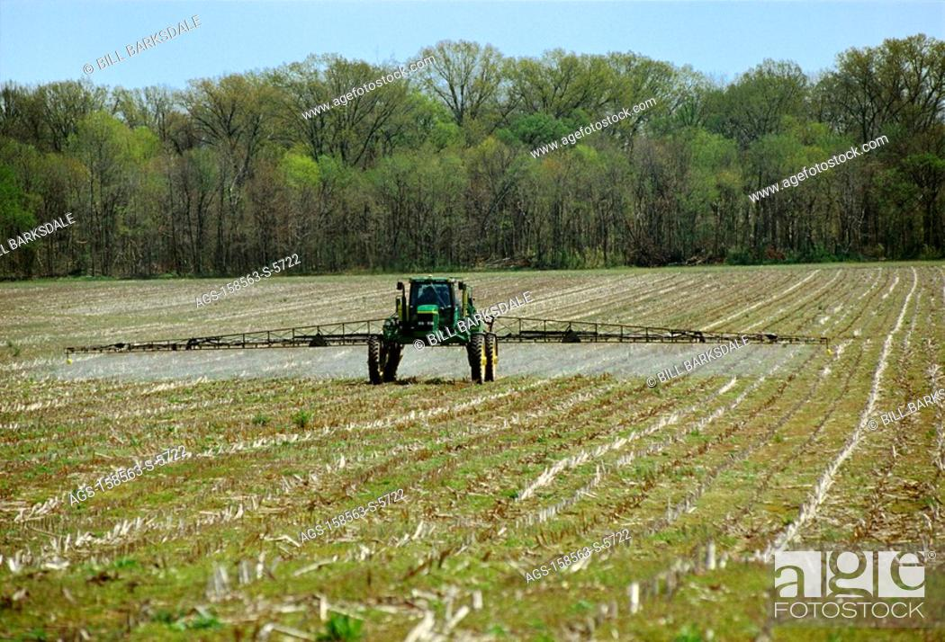 Stock Photo: Agriculture - Applying burndown herbicide to a field of corn stubble in Spring prior to planting no-till cotton / TN.