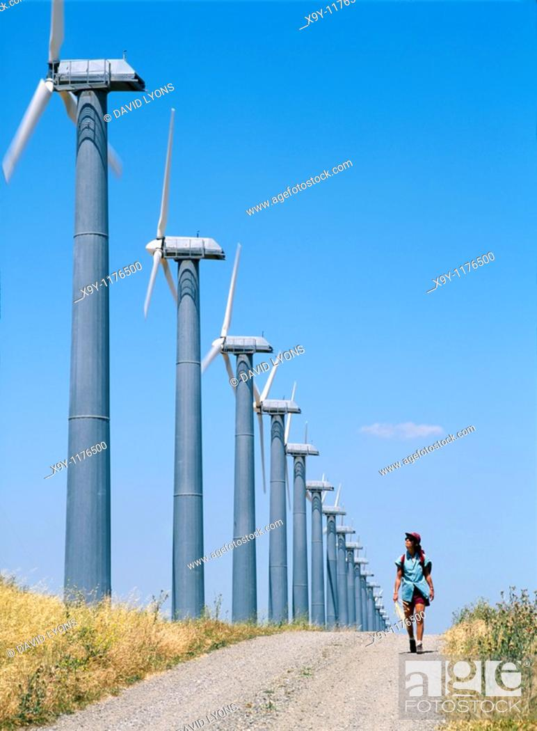 Stock Photo: Woman walking on track beside wind turbines, part of the massive wind farm complex at Altamont near Livermore, California, USA.