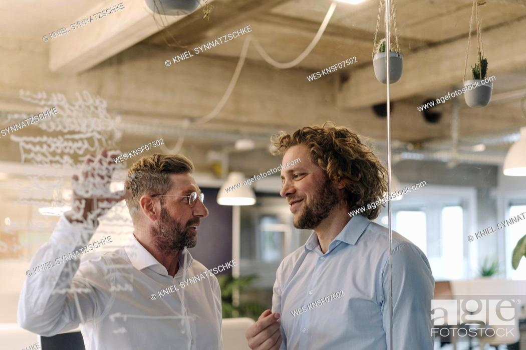 Stock Photo: Two businessmen working on a project in office.