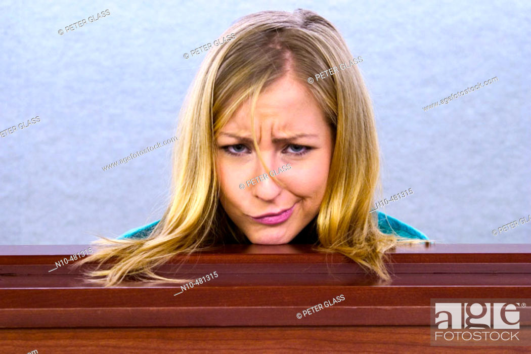 Stock Photo: Young blond woman's head resting on a ledge in an office building.