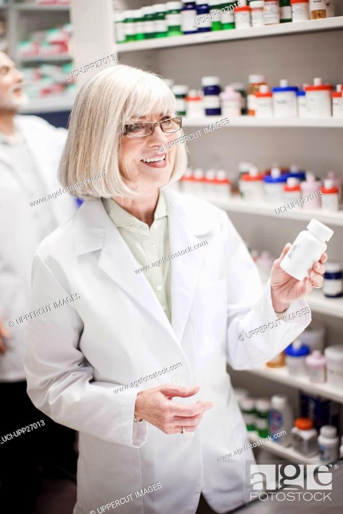 Stock Photo: Pharmacist holding prescription bottle.