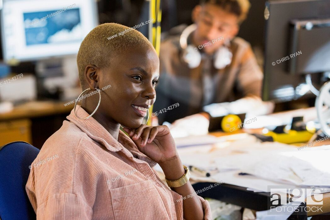 Stock Photo: Smiling creative businesswoman working in office.