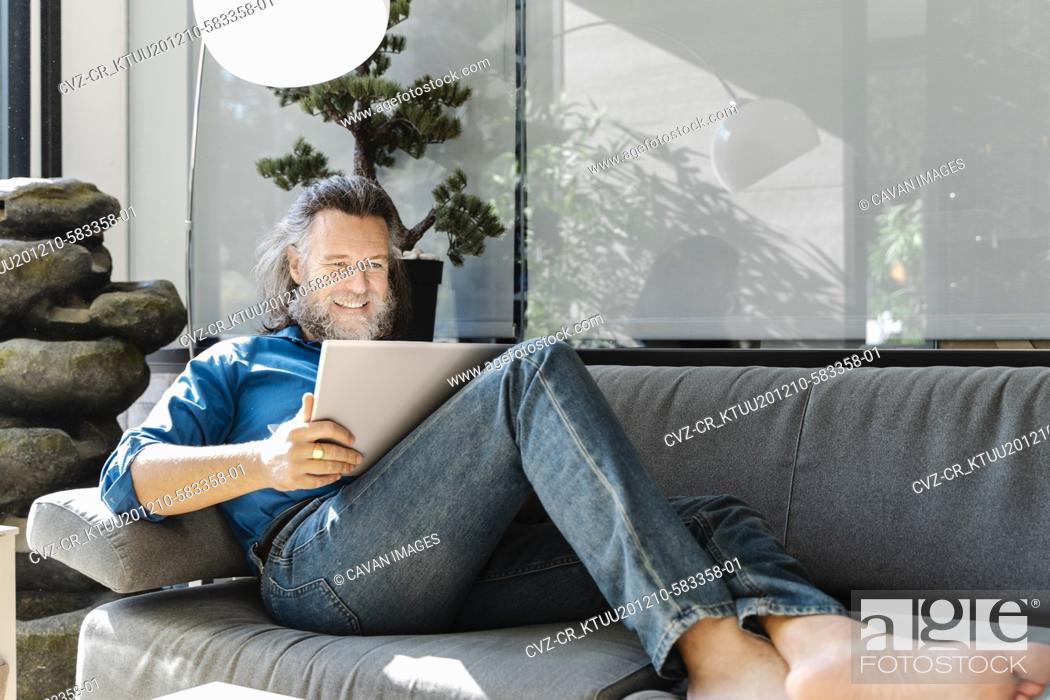 Stock Photo: Mature man with a beard smiling and working with his laptop on a sofa at home. Business concept.