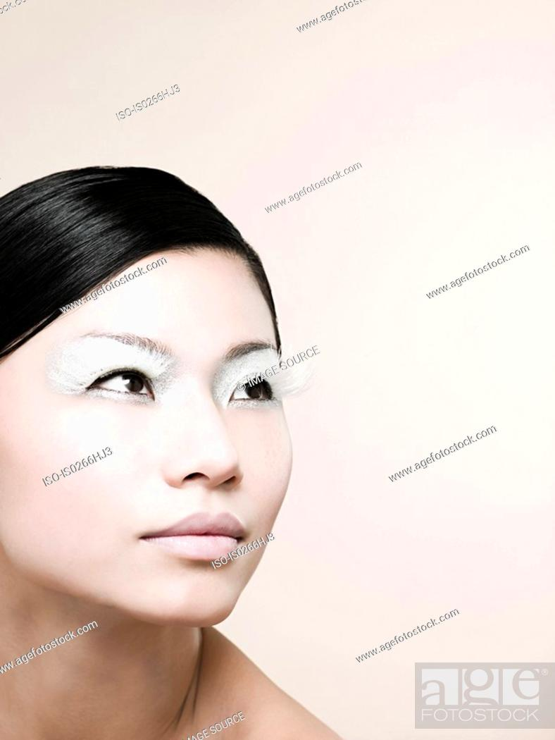 Stock Photo: A young woman wearing white false eyelashes.